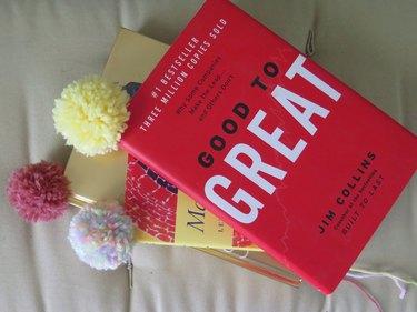 Using the yarn pompom bookmarks.