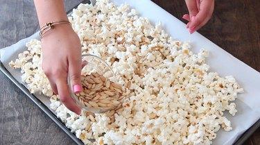 Adding pumpkin seeds to popcorn on cookie sheet.