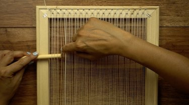 Using a round dowel as a shed stick for weaving on DIY simple frame loom.