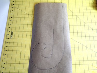 """A """"J"""" shape drawn on brown craft paper."""