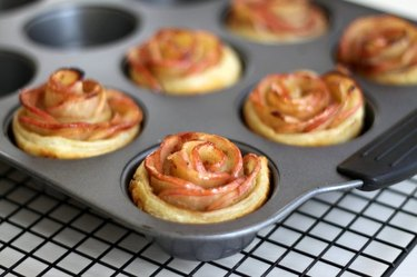 A muffin tin full of floral apple mini pies