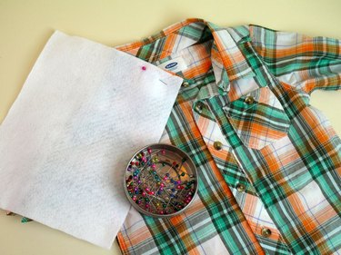 Felt piece pinned to the collar of the plaid shirt.