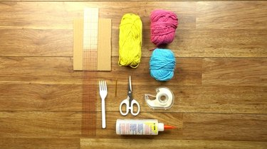 Materials for weaving coasters on a cardboard loom.