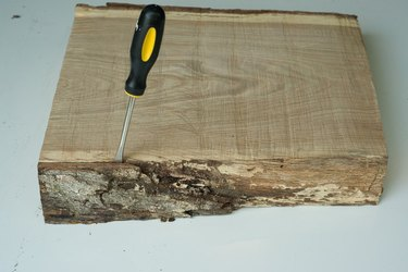 Take off excess bark with a screwdriver and hammer.