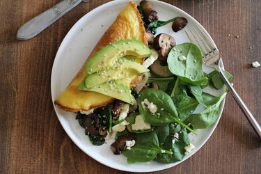 Vegetarian omelet with sauteed mushrooms, onions and spinach served on a plate.