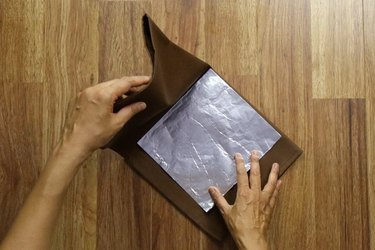 Inserting aluminum foil into the folded napkin for structure.