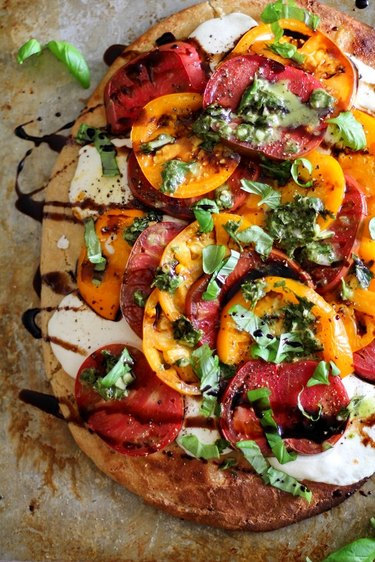 Pizza with mozarella, tomatoes, and balsamic reduction