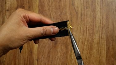 Clamping the end of a cut zipper to make a bracelet.