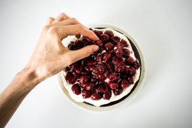 Hand placing some extra cherries on top of the cream and cake layer.
