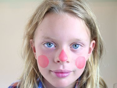 A childs face with peach make up on her cheeks and nose.