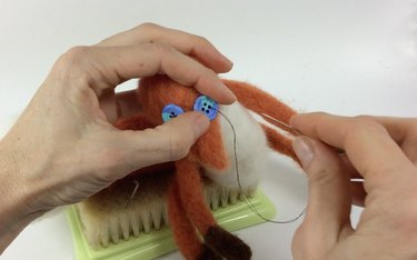 Female hands sewing button eyes onto a needle felted fox.