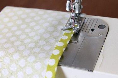 Costura do tecido para a bainha no sentido do comprimento