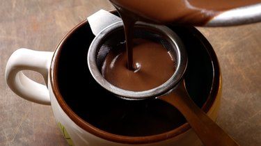 Straining low-carb, drinking chocolate into a mug to serve.