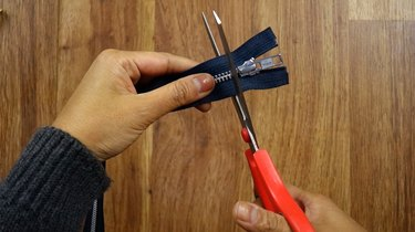 Cutting off the end of a zipper to make a knotted zipper bracelet.