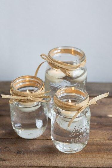 Three mason jars with floating candles.