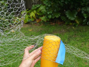 A baseball bat under the chicken wire at the shoulders.