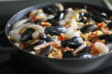 raw seafood on top of paella mixture