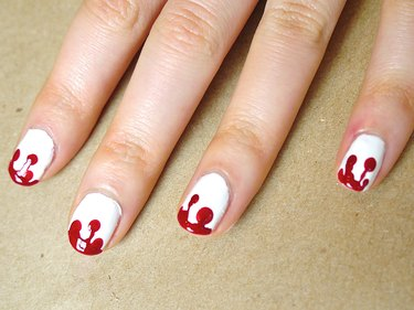 Red polish painted at the tips of the nails.