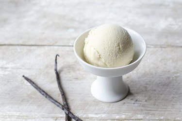 A scoop of ice cream in a bowl next to two vanilla bean pods