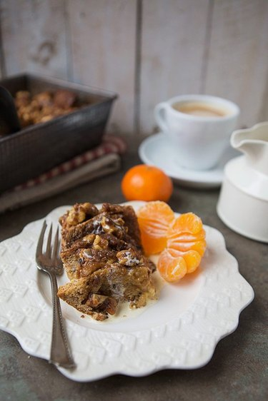 A slice of  French toast breakfast bake served with tangerines and coffee.