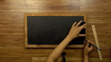 Marking placement of front-mounting cabinet pulls for DIY chalkboard serving tray.