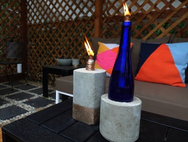 DIY concrete tabletop tiki torches out of used glass bottles on outdoor coffee table.