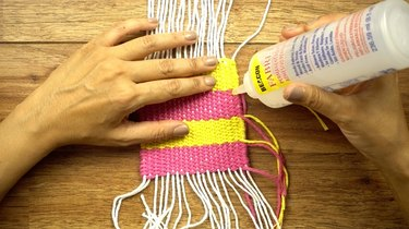 Tacking down loose tail of yarn after weaving in.