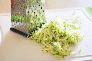 Grate the zucchini and then the cheese.