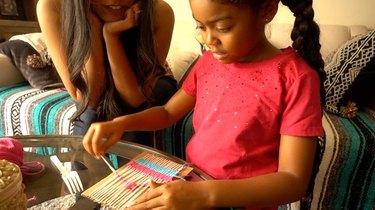 Mom and little girl making DIY coasters on cardboard loom.