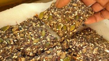 Breaking apart healthy seed and nut crispbread crackers.