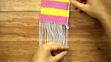 Finished edges of coasters woven on a cardboard loom.