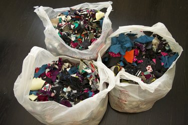 Three grocery bags of fabric scraps.
