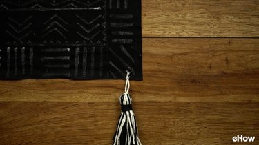 Gluing tassel on DIY mudcloth-inspired wall hanging.