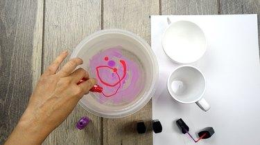 Mixing two nail polish colors for nail polish marbled mugs.