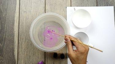 Preparing to dip nail polish marbled mugs into water.