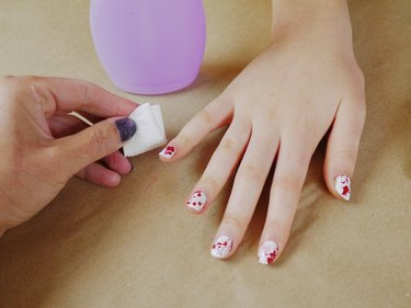 A cotton pad and polish remover cleaning around the nails.