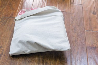 Inserting the patio cushion into the canvas cushion cover