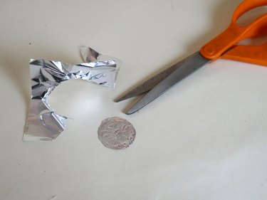 Scissors and a cut out foil circle.