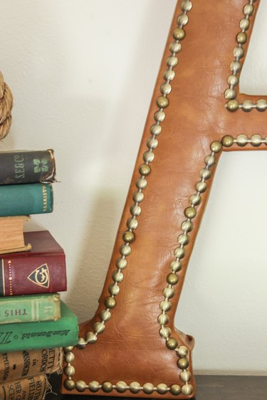 Close shot of finished leather monogram with nailhead trim