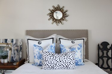 Bed with pillows and a gray padded headboard