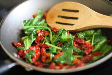 Sun-dried tomatoes, basil and spinach in a skillet