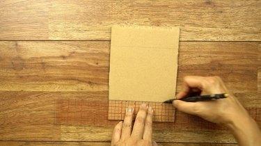 Drawing guidelines for weaving coasters on a DIY cardboard weaving loom.