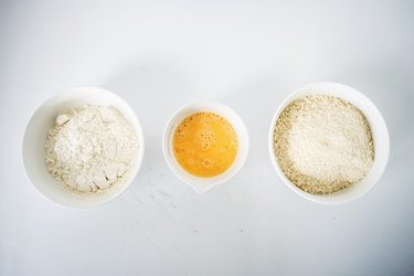 Flour, eggs and bread crumbs in three separate bowls.