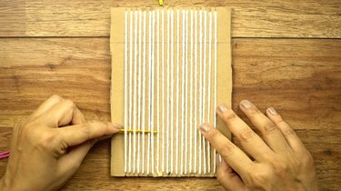 Weaving DIY coasters on a cardboard loom.