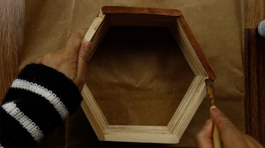 Staining DIY popsicle stick hexagon shelves with gel wood stain.