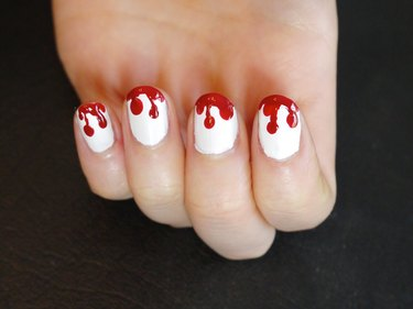 Blood dripping from the tips to the middle of the nails.