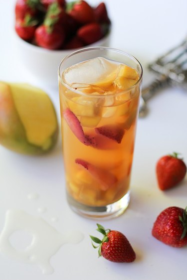 Glass of tropical sangria next to some fresh strawberries.