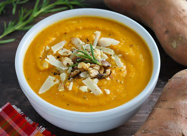 Sweet potato soup topped with cheese, pepper, and walnuts.