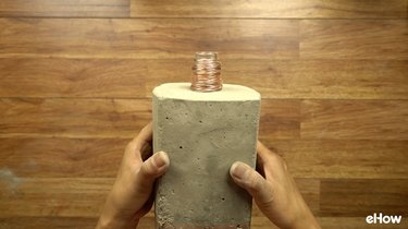 Decorating DIY concrete tabletop tiki torches out of used glass bottles.