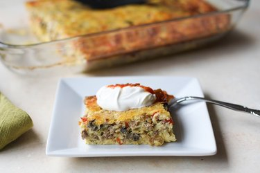 Piece of breakfast casserole with sour cream and salsa on top